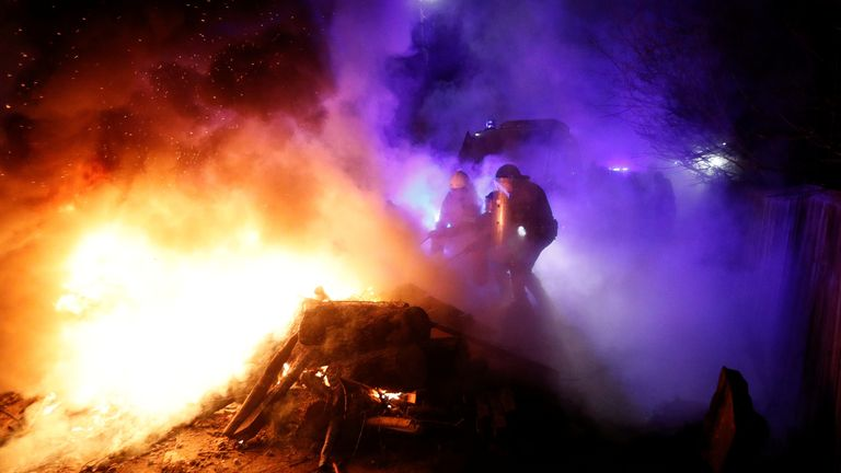 Police officers and firefighters work to the clear the way after demonstrators blocked a road