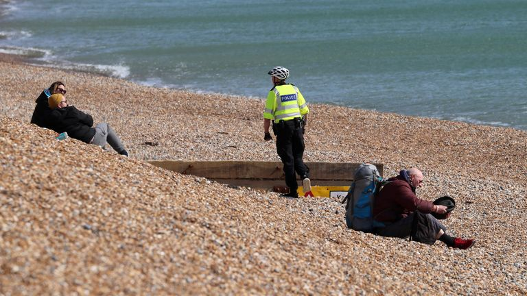 An officer tells people to leave Brighton beach as the public has been urged to stay at home
