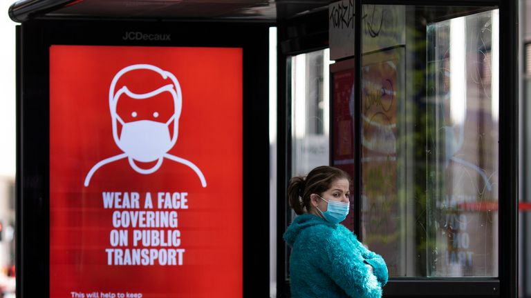 LONDON, ENGLAND  - MAY 18: A woman wearing a face mask stands at a bus stop next to a sign about wearing face masks on public transport on May 18, 2020 in London, England. The British government has started easing the lockdown it imposed two months ago to curb the spread of Covid-19, abandoning its 'stay at home' slogan in favour of a message to 'be alert', but UK countries have varied in their approaches to relaxing quarantine measures. (Photo by Dan Kitwood/Getty Images)