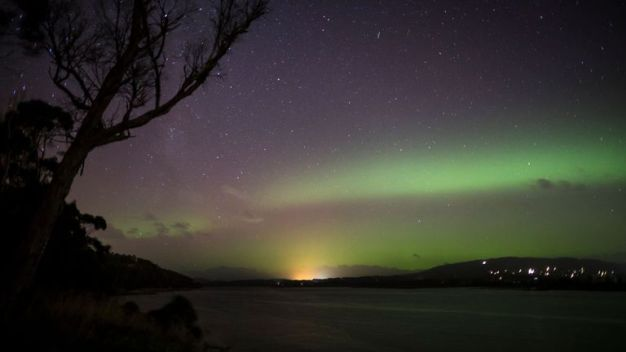 "The Aurora Australis, or ""Southern Lights"" light up over the Mersey River in Devonport on March 27, 2017 in Devonport, Australia. Aurora Australis, also known as the Southern Lights, happens when the sun releases a massive burst of solar wind and magnetic fields into space. These solar winds carry particles which interact with earth's magnetic field, colliding to produce energy releases in the form of auroras. (Photo by Heath Holden/Getty Images)"