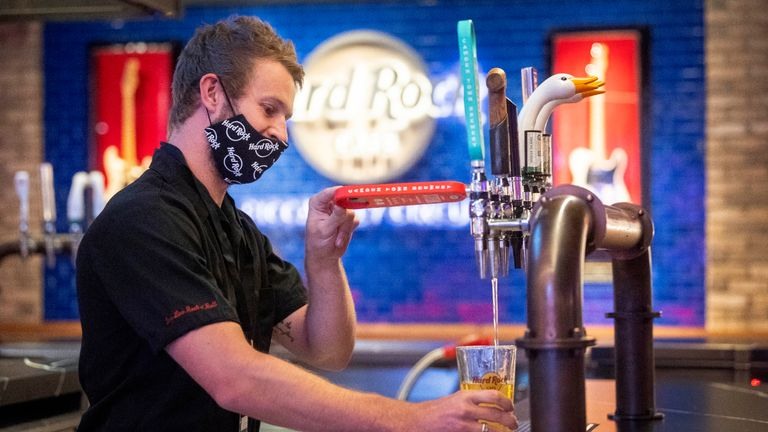 A bartender wears PPE as he pulls a pint behind the bar of the Hard Rock Cafe's European flagship restaurant in Piccadilly Circus, London, as it prepares to reopen to members of the public when the lifting of further lockdown restrictions in England comes into effect on Saturday.
