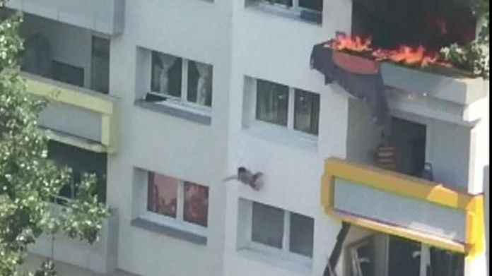 The boy jumps out the window and is grabbed by the crowd below
