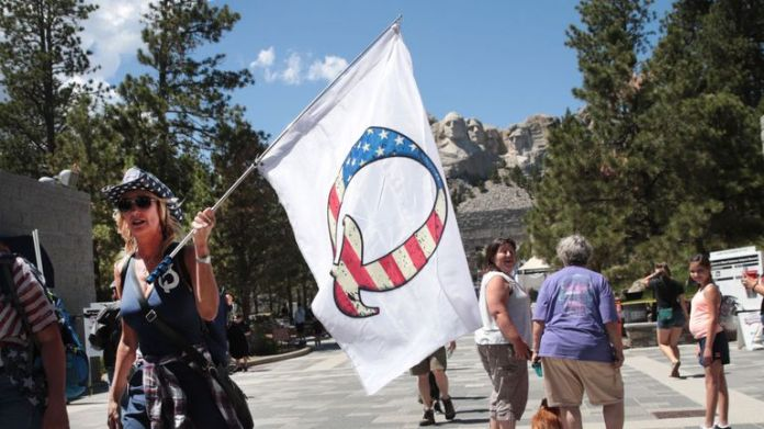 KEYSTONE, SOUTH DAKOTA - JULY 01: A Donald Trump supporter holding a QAnon flag visits Mount Rushmore National Monument on July 1, 2020 in Keystone, South Dakota. President Donald Trump is expected to visit the monument and speak before a fireworks display begins on July 3. (Photo by Scott Olson / Getty Images)