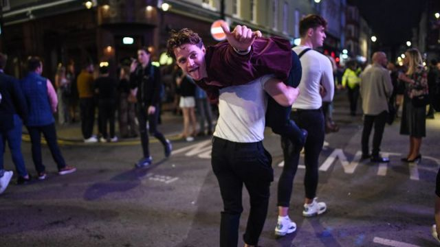 A man is seen being carried on his friend's shoulders in Soho