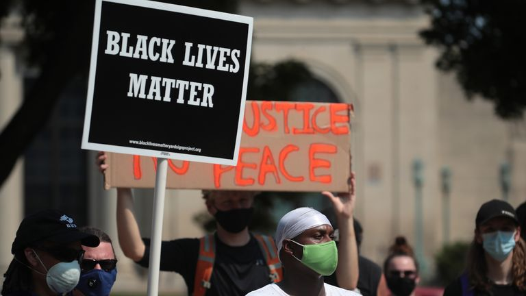 KENOSHA, WISCONSIN - AUGUST 24: A Black Lives Matter sign is held up as people gather in front of the police station the day after a Black man was shot by police causing outrage and local unrest in the city on August 24, 2020 in Kenosha, Wisconsin. Kenosha Police shot a Black man multiple times in the back yesterday night as he entered the driver's side door of a vehicle. The man reportedly identified as Jacob Blake, was hospitalized in Milwaukee in serious condition. (Photo by Scott Olson/Getty Images)