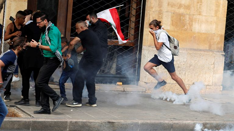 Demonstrators run away from tear gas fired by riot police