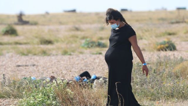 A pregnant woman walks near the coast of Dungeness after arriving in the UK. Pic: Susan Pilcher
