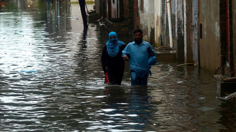 Residents wade through the flooded streets of Karachi