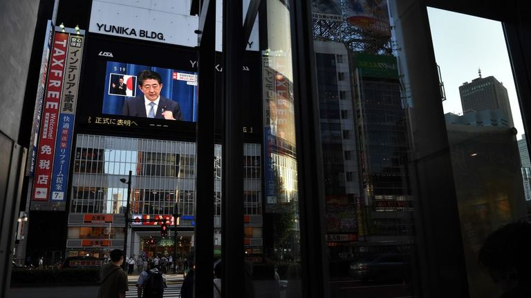 Mr Abe is seen on a large screen giving his news conference