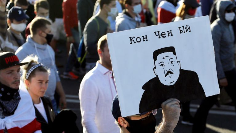 """A man carries a placard depicting Belarus' President as North Korean leader Kim Jong-un and reading """"Washed-up"""" during a demonstration called by opposition movement for an end to the regime of authoritarian leader in Minsk on September 20, 2020 - Belarus President Alexander Lukashenko, who has ruled the ex-Soviet state for 26 years, claimed to have defeated opposition leader Svetlana Tikhanovskaya with 80 percent of the vote in the August 9, elections. (Photo by - / TUT.BY / AFP) (Photo by -/TUT"""