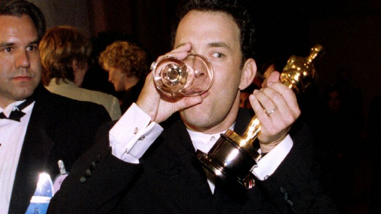 """Actor Tom Hanks sips a glass of water at the Governor's Ball March 27 as he holds the Oscar he won as best actor for his role in """"Forrest Gump"""" at the 67th Academy Awards in Los Angeles"""