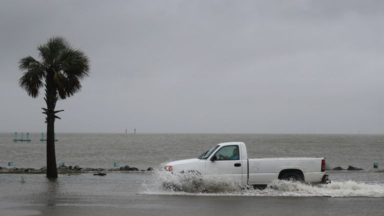 Hurricane Sally Makes Landfall On Gulf Coast BAYOU LA BATRE, ALABAMA - SEPTEMBER 15: A driver navigates along a flooded road as the outer bands of Hurricane Sally come ashore on September 15, 2020 in Bayou La Batre, Alabama. The storm is threatening to bring heavy rain, high winds and a dangerous storm surge from Louisiana to Florida. (Photo by Joe Raedle/Getty Images)