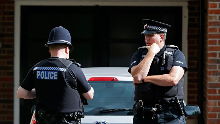 Police officers stand outside the house of Saad al-Hilli and his family in Claygate near London in 2012