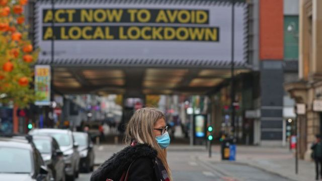 A woman wearing a face mask in Manchester city centre as the row over Greater Manchester's coronavirus status continues.