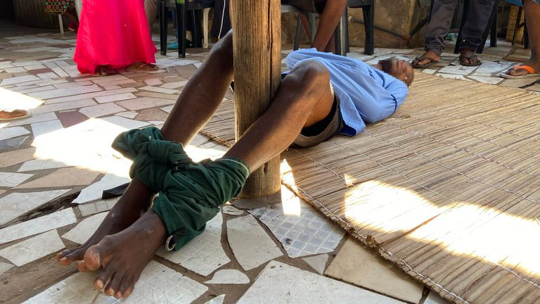"A man with a mental health condition lies on the floor with his legs tied around a wooden pole and his arms in a straitjacket at a church outside Maputo, Mozambique. The church pastor provides spiritual guidance and uses the word of God to ""fight evil spirits."""