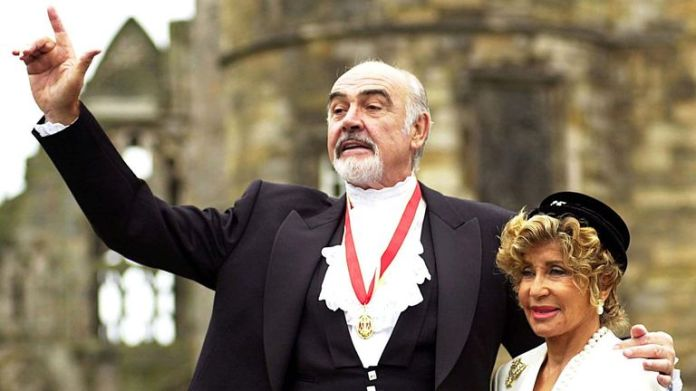 Sir Sean Connery, with his wife Micheline (right), poses for the photographers after being officially knighted by .. Sir Sean Connery, with his wife Micheline (right), poses for the photographers after being officially knighted by the British. [Queen Elizabeth] at Holyrood Palace in Edinburgh on July 5th. [The Scottish screen legend, famous for his role as James Bond, was honoured two years after he was reportedly denied a knighthood because of his passionate Scottish nationalism. ]DOWNLOAD PHOTO Date: 07/05/2000 12:00 Dime
