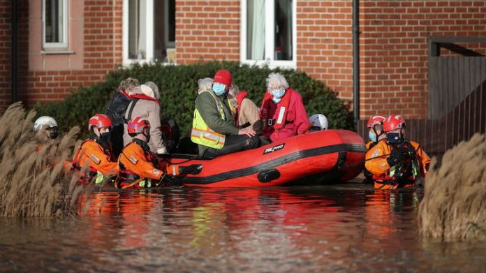 Residents of a care home are evacuated after the river Weaver burst banks in Northwich, Britain, January 21, 2021. REUTERS/Molly Darlington