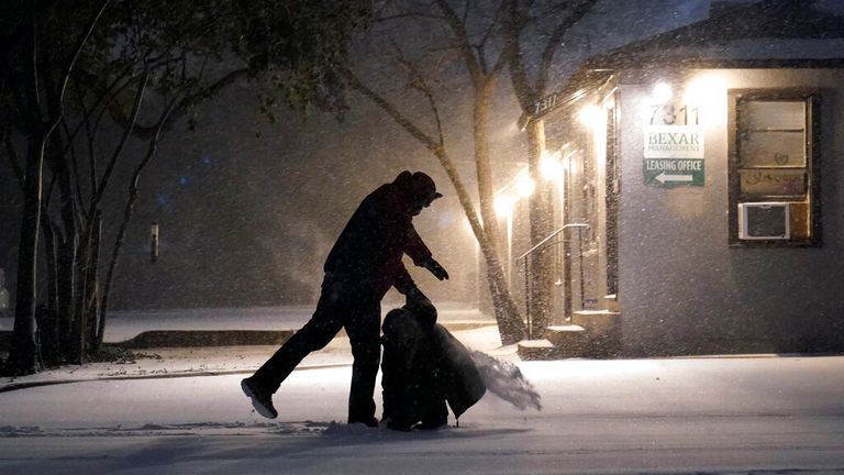 Two people play in the snow in San Antonio, Texas