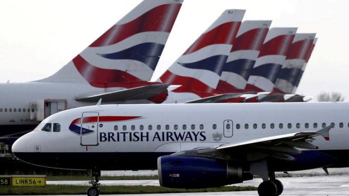FILE PHOTO: A British Airways plane walks past the rear fins of an aircraft parked near Terminal 5 at Heathrow Airport in London, Britain March 14, 2020