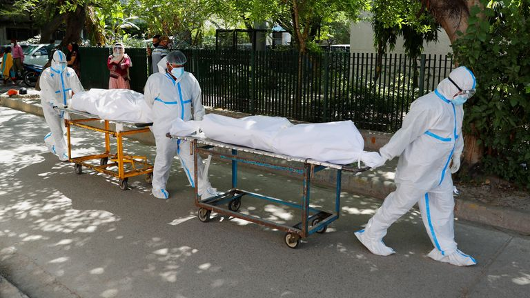 Health workers wearing personal protective equipment (PPE) carry bodies