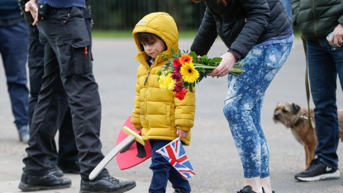A child and her mother arrive to lay flowers outside Windsor Castle