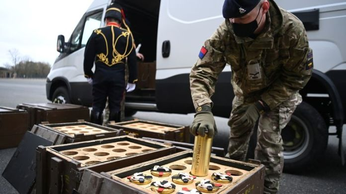 A member of the Royal Horse Artillery of the King's Troop places empty shells in boxes before a cannon fires