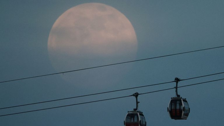 The full moon, also known as the supermoon, rises over the Emirates Air Line cable car on April 26, 2021 in London, United Kingdom. REUTERS / Hannah McKay TPX PICTURES OF THE DAY
