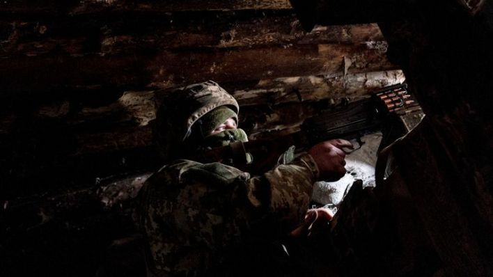 A Ukrainian serviceman keeps ready a machine gun in his shelter near the front-line town of Krasnohorivka, eastern Ukraine, Friday, March 5, 2021. The country designated 14,000 doses of its first vaccine shipment for the military, especially those fighting Russia-backed separatists in the east. But only 1,030 troops have been vaccinated thus far. In the front-line town of Krasnohorivka, soldiers widely refuse to vaccinate. (AP Photo/Evgeniy Maloletka)