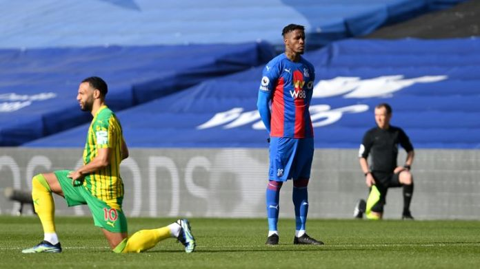 Wilfried Zaha stands while other players take a knee in March
