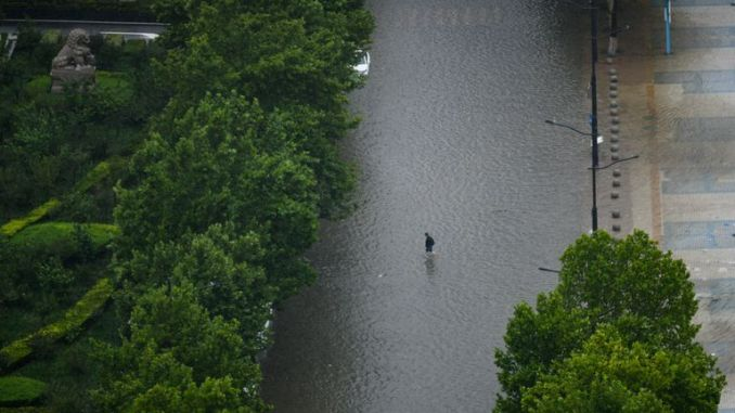 A person walks in the waterlogging caused by rainstorm in Zhengzhou city, central China's Henan province, 20 July 2021. (Imaginechina via AP Images)