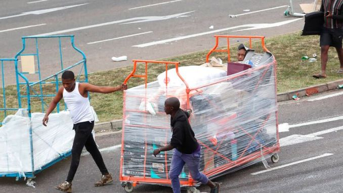 People make their way with good on a trolley taken from a store in Durban, South Africa, Tuesday July 13, 2021