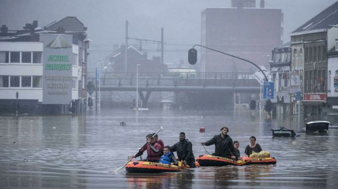 People use rubber rafts in floodwaters after the Meuse River broke its banks during heavy flooding in Liege, Belgium on Thursday