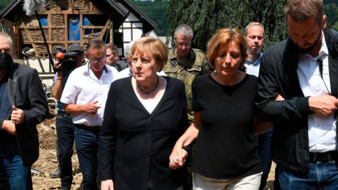 German Chancellor Angela Merkel held hands with local politicians in the flood-hit village of Schuld. Pic: AP