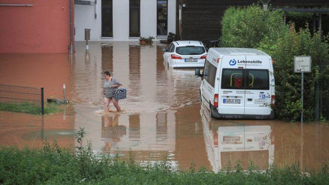 A woman wades across floodwater in Gross-Vernich, North Rhine-Westphalia, Germany