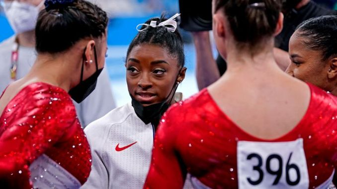 Simone Biles talks to her US team-mates during the final