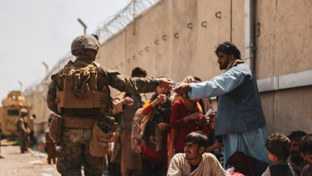 A US Marine passes out water to evacuees at Kabul's international airport