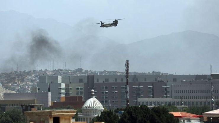 A U.S.Chinook helicopter flies over the city of Kabul, Afghanistan, Sunday, Aug. 15, 2021. Helicopters are landing at the U.S. Embassy in Kabul as diplomatic vehicles leave the compound amid the Taliban advanced on the Afghan capital. (AP Photo/Rahmat Gul).