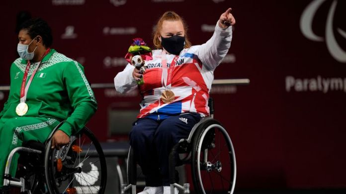 Britain's Louise Sugden points to students cheering for her after receiving a bronze medal in women's -86kg powerlifting final at the Tokyo 2020 Paralympic Games, Monday, Aug. 30, 2021, in Tokyo, Japan. (AP Photo/Kiichiro Sato