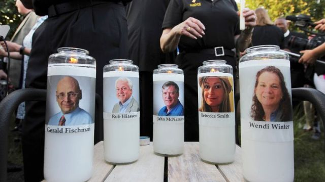 FILE - In this June 29, 2018, file photo, images of five employees of the Capital Gazette newspaper adorn candles during a vigil across the street from where they were slain in the newsroom in Annapolis, Md. Nearly three years after five people at the Capital Gazette newspaper were killed, a Maryland judge discussed plans Tuesday, April 13, 2021, for holding the second part of the shooter's trial under COVID-19 court protocols. (AP Photo/Jose Luis Magana, File)