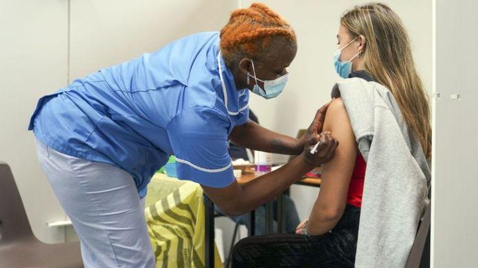 Nurse Marvis Birungi (left) gives a vaccine injection to Oxford Brookes University student Eleanor Seddon