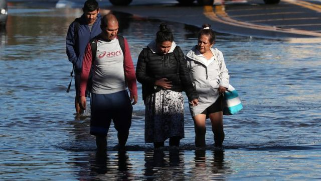 Local residents wade through floodwaters as they escape their homes after the remnants of Tropical Storm Ida brought drenching rain, flash floods and tornadoes to parts of the northeast in Mamaroneck, New York