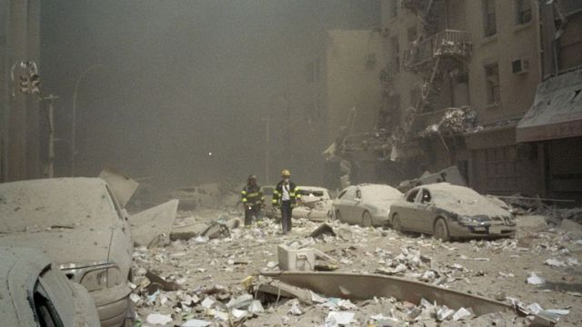 FIremen walk through a dust and debris covered street in lower Manhattan Tuesday, Sept. 11, 2001, after a terrorist attack at the World Trade Center. Two jet planes were crashed into the twin towers, collapsing them and covering the area with the debris.(AP Photo/Richard Cohen)