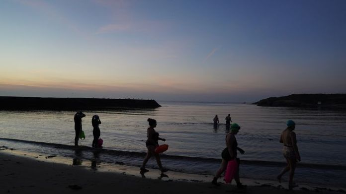 Sea swimmers head out before sunrise at Cullercoats Bay on the North East coast. Temperatures are forecast to reach up to 30C in parts of the UK