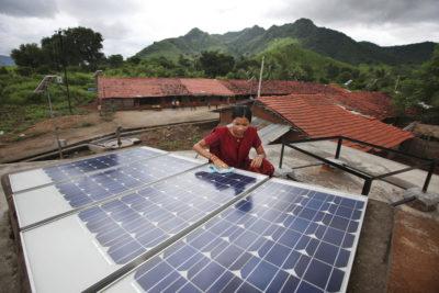 Meenakshi Dewan, a solar engineer, inspects solar panels in the rural community of Tinginaput, India.