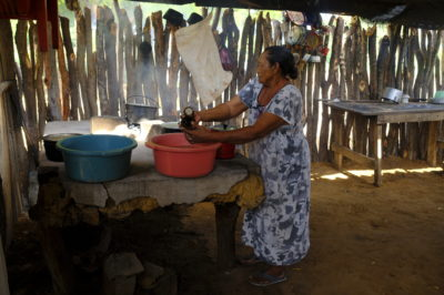 A woman prepares a meal in a traditional Wayúu home.