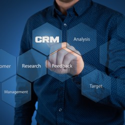 Man in blue shirt pointing to digital CRM button