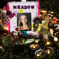 A photograph of Meadow Pollack at the base of one seventeen crosses at a candlelight vigil for the victims of the  shooting at Marjory Stoneman Douglas High School, in Parkland, Fla, on February 16, 2018 (Greg Lovett/The Palm Beach Post/Zuma Press/TNS)