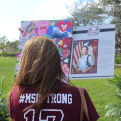 In Remembrance. English teacher Stacey Lippel stops to remember Alaina Petty. Lippel stopped at every panel to remember each of the 17 students and faculty who were memorialized in the Parkland Hearts panels. Photo by Farrah Nickerson
