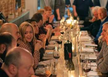 Attendees of a Farm to Fork 101 dinner are seated at a candlelit table.