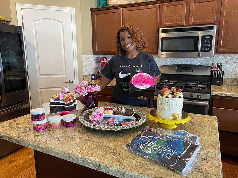 Aunjanaya Ramdath poses in her kitchen with a variety of baked goods.